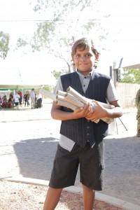 Local Tennant Creek school boy dressed as a 1915 paper boy hands newspapers to arriving guests.