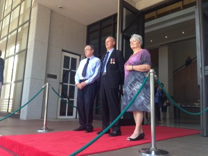 His Honour the Honourable John Hardy AO Administrator of the Northern Territory, Rowan and Mary Borella wait on the steps of Parliament House to receive the Victoria Cross.